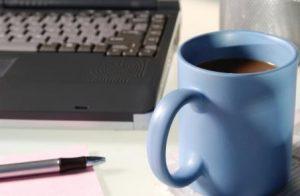 keyboard and coffee mug denoting office work
