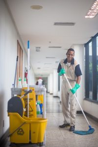 male cleaner working in an office corridor